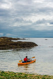 Man in Paddle Boat at the Coast of Ireland Stock Photo