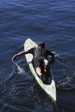 Man on paddleboard. High angle view of man in wetsuit on paddle-board in sea Stock Image