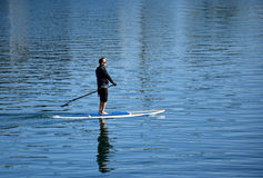 Man on paddleboard in Dana Point Harbor, California. Image shows a man on a paddleboard in Dana Point Harbor, California. Stand up paddleboarding is a popular Stock Photography