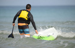 Man with paddleboard and paddle heading out into the ocean weari Stock Photos