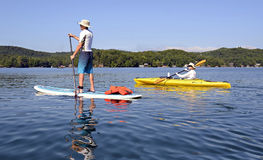 Man on Paddleboard Woman on Kayak Stock Image