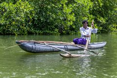 A man paddles an outrigger canoe in Sri Lanka. royalty free stock photography