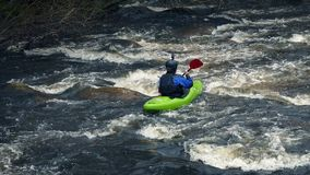 Man in kayak goes past on wild river. Man paddles past in kayak on river in the wilderness stock footage
