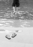 Man paddles water flip flop thongs. Man paddles in shallow water leaving flip flop thongs on bank Stock Photos