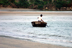 Man Paddling. Man in bamboo basket boat heading to shore Royalty Free Stock Images