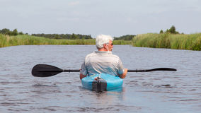 Man paddling in a blue kayak Stock Image