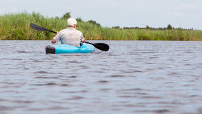Man paddling in a blue kayak Stock Photography