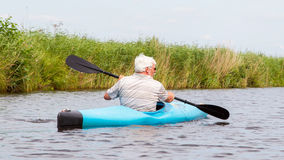Man paddling in a blue kayak Stock Photos