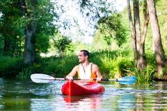 Man paddling with canoe or kayak on river Stock Image