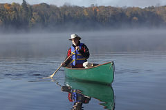 Man Paddling a Canoe with a Small White Dog in the Bow. Man Paddling a Canoe on a Lake in Autumn with a Small White Dog in the Bow - Ontario, Canada royalty free stock photos