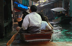 Man Paddling on Floating Market, Thailand. Sunny day, taking many passengers in his wooden boat Royalty Free Stock Image