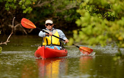 Man paddling in a kayak in Florida Stock Photo
