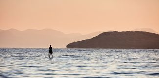 A man paddling on a paddleboard in the open sea. Silhouette of a man standing on the sea with a paddle in his hand Stock Photography