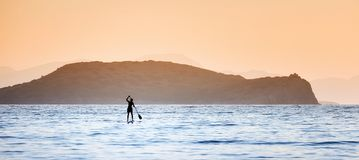 A man paddling on a paddleboard in the open sea. Silhouette of a man paddling on a surfboard in the open sea. He is rowing in front of an island at sundown with Stock Image