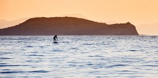 A man paddling on a paddleboard. Silhouette of a man paddling on a surfboard in the open sea. He is struggling in front of an island at sunset with beautiful Royalty Free Stock Photo