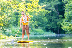 Man paddling on SUP in river Stock Photo