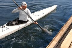 Man paddling a white kayak. On the river near the shore. Kayaking concept royalty free stock images