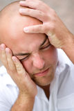 Man In Pain. A young man that looks to be losing his mind and grabbing his head in desperation Royalty Free Stock Photos
