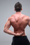 Man with pain on back. Back pain injury on fit adult man Stock Photos