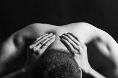 A man with pain in the back and neck. Close up of holding on the neck on a dark background. A man with pain in the back and neck. Close up of holding on the stock photography