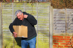 Man in pain carrying heavy box. Shoulder strain. An elderly man in pain carrying a very heavy box. The box is too heavy for him and he will cause injury to Stock Photos
