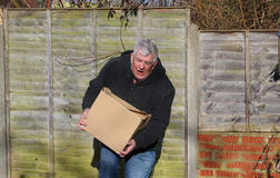 Man in pain carrying heavy box. Too heavy. An elderly man in pain carrying a very heavy box. The box is too heavy for him and he will cause injury to himself Royalty Free Stock Photo