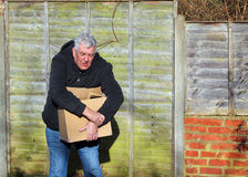 Man in pain carrying heavy box. Wrist strain. An elderly man in pain carrying a very heavy box. The box is too heavy for him and he will cause injury to himself Royalty Free Stock Photography