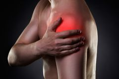 Man with pain in shoulder on black background Stock Photography