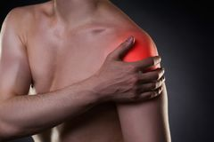 Man with pain in shoulder on black background Royalty Free Stock Photos