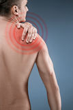 Man with pain in shoulder. Pain in the human body. Black and white photo with red dot royalty free stock photo