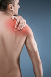 Man with pain in shoulder. Pain in the human body. Black and white photo with red dot royalty free stock photos