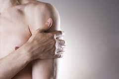 Man with pain in shoulder. Pain in the human body. On a gray background stock photos