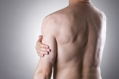 Man with pain in shoulder. Pain in the human body. On a gray background stock images