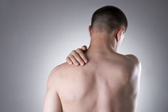 Man with pain in shoulder. Pain in the human body. On a gray background royalty free stock image