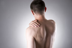 Man with pain in shoulder. Pain in the human body. On a gray background royalty free stock photo