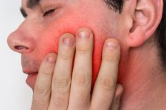 Man with a painful expression is having toothache. Body pain concept stock photography