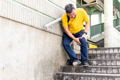 Man with painful knee struggle walking down flight of stairs stock photography
