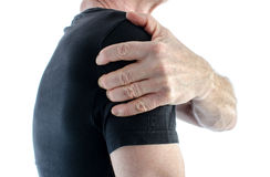 Man with painful shoulder. Man holding his sore shoulder royalty free stock image