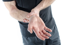 Man with painful wrist. Man holding his sore wrist stock image