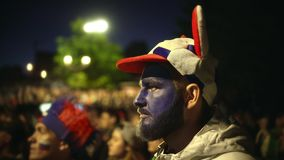 Man with paint face enthusiastically watche football match background crowd 4k. stock footage