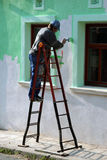 Man paint the house wall. Man color the house wall Royalty Free Stock Images