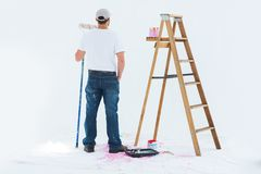 Man with paint roller standing by ladder Royalty Free Stock Photo