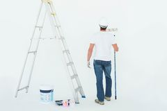 Man with paint roller standing by ladder Royalty Free Stock Photography