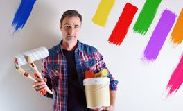 Man with paint tools in hands and painted colorful wall royalty free stock photos