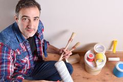 Man with paint tools on hands top elevated view. Man with paint tools and white wall y parquet floor behind. Diy home concept. Top elevated view. Horizontal royalty free stock photos