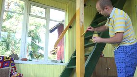 Man paint yellow colour wooden column near stairs to loft. 4K stock video