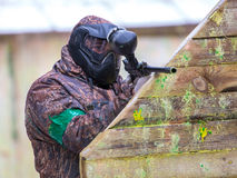 Man with paintball gun behind fortification with paint splashes. Outdoors Royalty Free Stock Photography