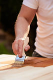 Man with paintbrush painting on a wooden table Royalty Free Stock Images