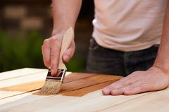 Man with paintbrush painting on a wooden table Royalty Free Stock Photos