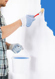 Man with paintbrush and pot painting wall Royalty Free Stock Photos